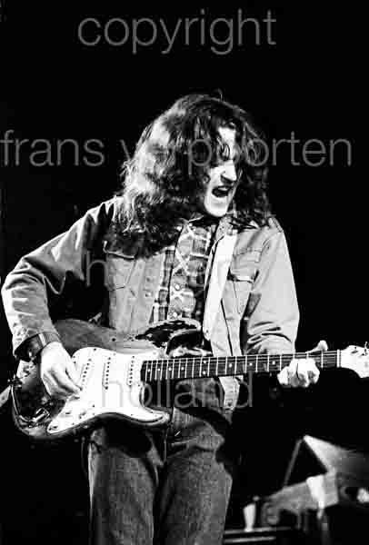 Rory Gallagher was born in Ballyshannon, County Donegal in 1948. His father Daniel was employed by the Irish Electricity Supply Board, who were constructing a hydro-electric power plant on the Erne River above the town. The family moved, first to Derry City, where his younger brother Dónal was born in 1949. His mother, Monica, and the two boys then moved to Cork, where the brothers were raised. Rory attended North Monastery School. Daniel Gallagher had played the accordion and sang with the Tír Chonaill Céilí Band whilst in Donegal; their mother Monica was a singer and acted with the Abbey Players in The Theatre in Ballyshannon where Monica once acted is now called the Rory Gallagher Theatre. Both sons were musically inclined and encouraged by their parents. At age nine, Gallagher received his first guitar from them. He built on his burgeoning ability on ukulele in teaching himself to play the guitar and perform at minor functions. After winning a talent contest when he was twelve, Gallagher began performing in his adolescence with both his acoustic guitar, and an electric guitar he bought with his prize money. However, it was his purchase three years later of a 1961 for £100 that became his primary instrument and most associated with him for the span of his lifetime Gallagher was initially attracted to after hearing on the radio. Donegan frequently covered blues and folk performers from the United States. He relied entirely on radio programs and television. Occasionally, the BBC would play some blues numbers, and he slowly found some song books for guitar, where he found the names of the actual composers of blues pieces. While still in school, playing songs by Buddy Holly and Eddie Cochran, he discovered his greatest influence in Muddy Waters. He began experimenting with folk, blues, and rock music. Unable to find or afford record albums. Source Wikipedia